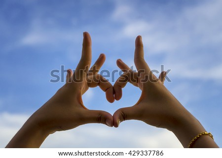 Heart symbol by hand, love sign on Blue sky background  - stock photo
