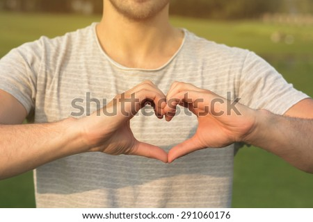 Heart symbol by man. Man making heart with his hands isolated on his T-shirt. - stock photo