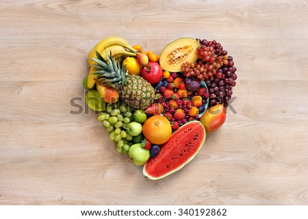 Heart symbol. Fruits diet concept. Healthy eating concept / food photography of heart made from different fruits on wooden table. High resolution product. - stock photo