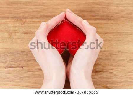 Heart symbol in hands. Concept of health, protection and love. Woman holding heart in her hands. On wooden background - stock photo