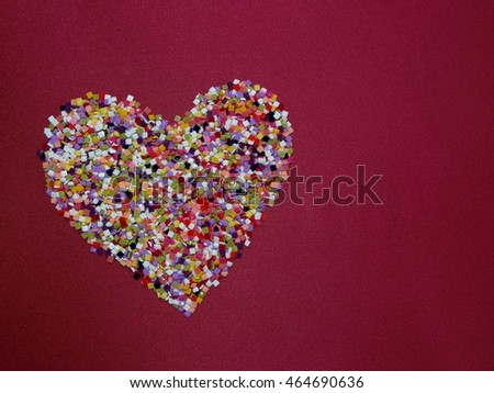 heart symbol made of colorful confetti on red silk