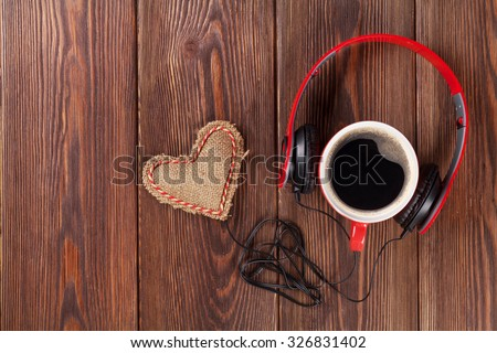 Heart toy with headphones and coffee cup on wooden table with copy space. Valentine's day concept. - stock photo