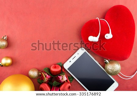 Heart with christmas ornaments and smartphone with earphones, on red with copy-space - stock photo