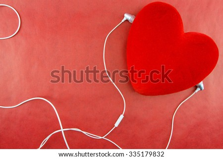 Heart with earphones closeup on red background - stock photo