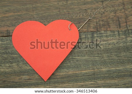 Heart with fishing hook. - stock photo