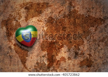 heart with national flag of ethiopia on a vintage world map crack paper background. concept - stock photo
