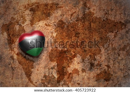 heart with national flag of libya on a vintage world map crack paper background. concept - stock photo