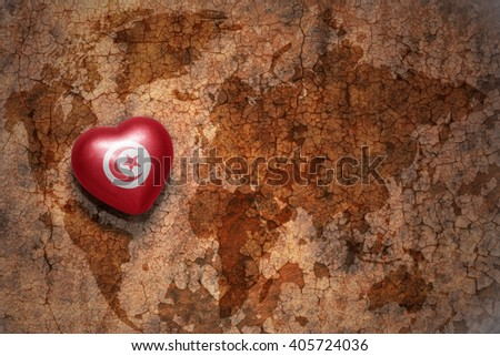 heart with national flag of tunisia on a vintage world map crack paper background. concept - stock photo