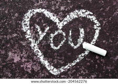 "heart with the word ""you"" drawn in chalk on concrete - stock photo"