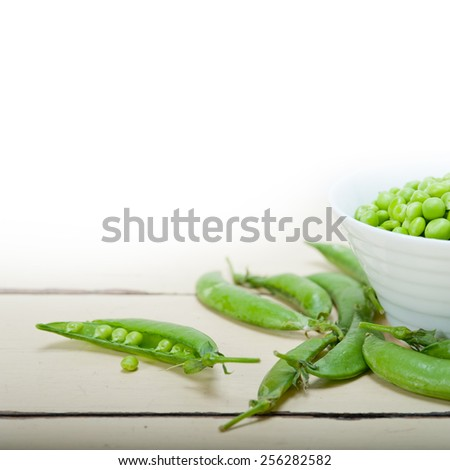hearthy fresh green peas  over a rustic wood table - stock photo