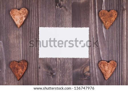 Hearts and paper card on wood background