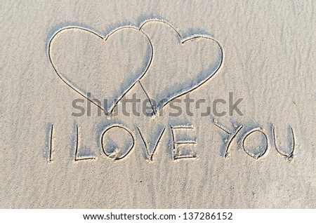 Hearts drawn with i love you text on the sand of a beach - stock photo