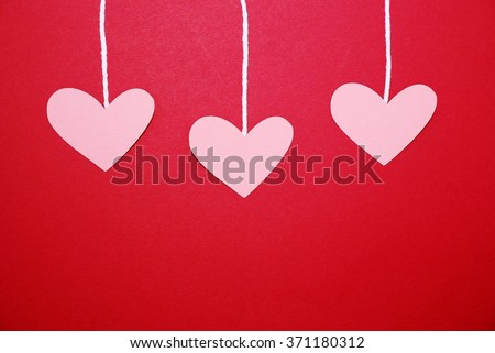 Hearts hanging from string on a red background, can be used for Valentine's Day or Mother's Day project - stock photo