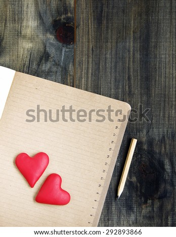 Hearts lie on a notepad with a pencil Valentine's Day