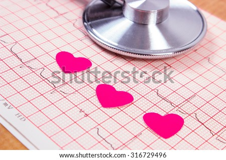 Hearts of paper and medical stethoscope lying on electrocardiogram graph, ecg heart rhythm, medicine and healthcare concept - stock photo