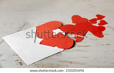 hearts of paper poured out of the envelope on the old desktop - stock photo