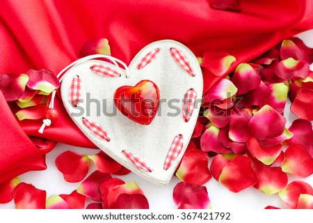 Hearts on a background of red petals and satin