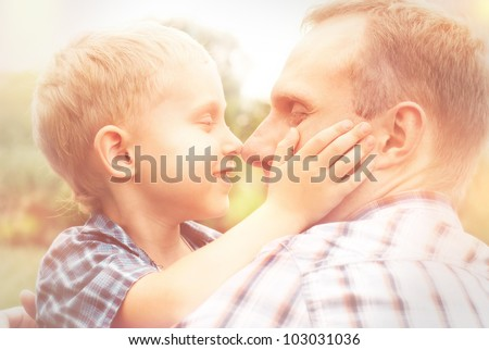 Heartwarming hugs little son and his father in warm sun shins - stock photo
