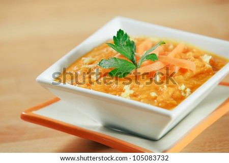 Hearty bowl of ginger carrot soup, topped wtih garnish. - stock photo