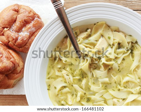 Hearty bowl of healing homemade chunky chicken noodle soup served with buttery dinner rolls on a wooden surface. - stock photo