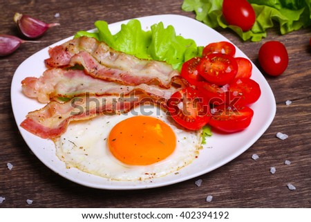 Hearty breakfast. Fried egg with bacon and tomatoes on a wooden background - stock photo