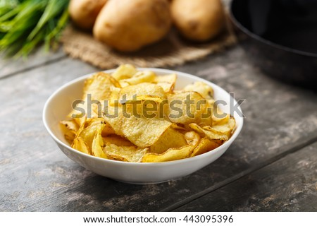 Hearty kettle cooked potato crisps served in a bowl. - stock photo