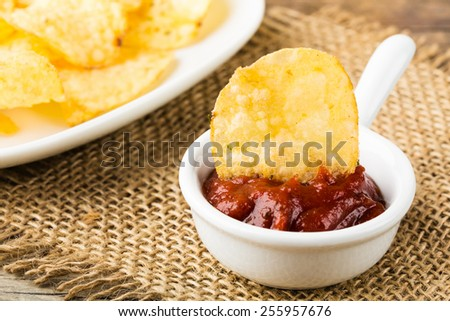 hearty potato chips with hot tomato dip served in a bowl. - stock photo