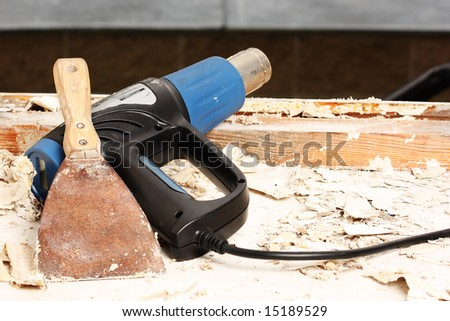 Heat gun and scraper for removing old paint during window renovation - stock photo