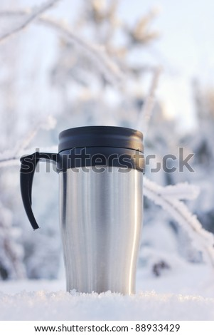 Heat protection-thermos coffee cup on winter day - stock photo