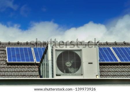 Heat Pump and Solar Panels on a Family House Roof - stock photo