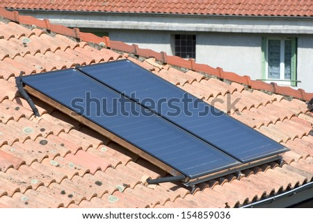 Heat solar water installed on a roof of Anduze, French city in the south-east of France. - stock photo