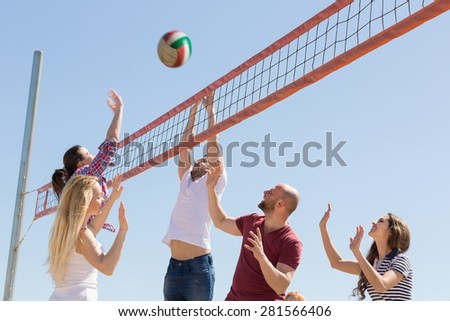 Heated active friends playing volleyball at sandy beach
