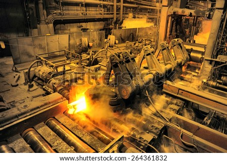 heated steel pigs on the rolling mill - stock photo