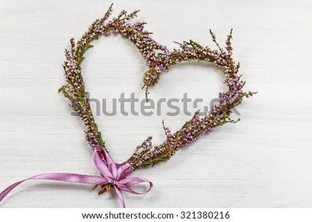 Heather (erica) door wreath in heart shape on wooden background, copy space - stock photo