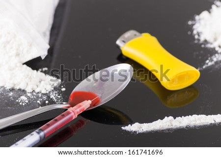 heating drugs in a spoon over a flame - stock photo