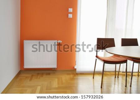 Heating Radiator on the Orange Wall - stock photo