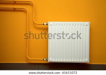 Heating radiator, orange wall - stock photo