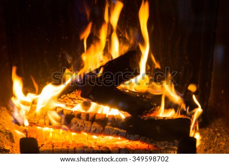 heating, warmth, fire and cosiness concept - close up of firewood burning in fireplace - stock photo