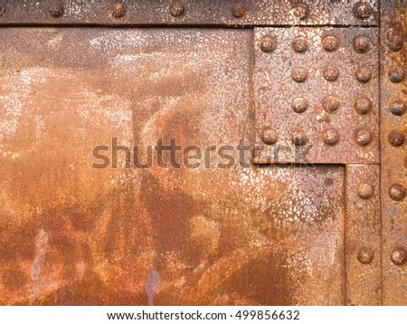 Heavily corroded iron panel of a riveted steel construction background texture pattern