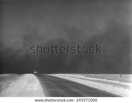 Heavy black clouds of dust rising over the Texas Panhandle. March 1936 photo by Arthur Rothstein. - stock photo