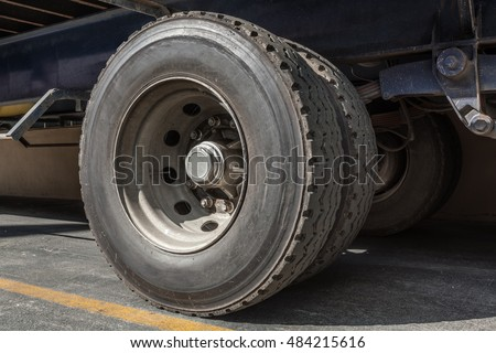 Heavy cargo truck wheel close up covered in dirt weathered and worn rubber tyre side perspective