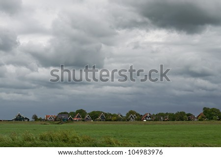 Heavy clouds over a typical Dutch village on a windy day. - stock photo