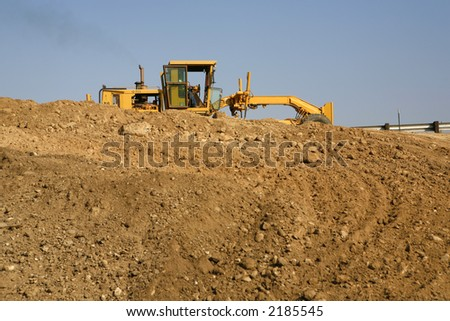 Heavy construction equipment working on a mound of dirt - stock photo
