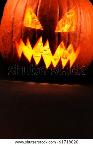 Heavy contrast photo of a carved evil pumpkin glowing.  Pulp and seeds still inside. - stock photo