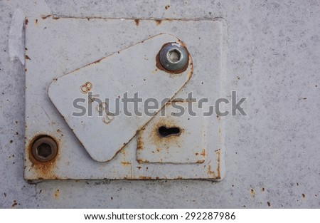 Heavy duty metal, steel lock, keyhole and cover plate on a steel security door, with an imprinted stamped number. Distressed and rusty. - stock photo