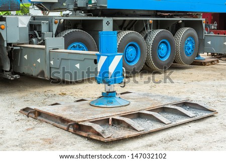 Heavy duty steel crane outrigger pad in construction site - stock photo