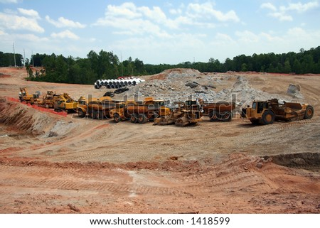 Heavy earth moving construction vehicles lined up in a row - stock photo