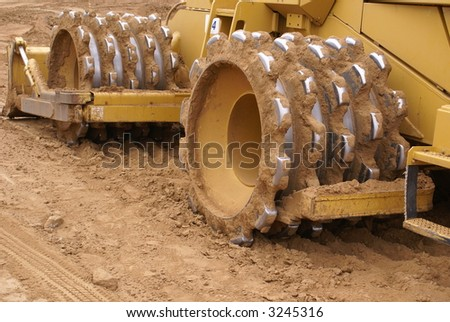 Heavy earth moving equipment prepares construction site for building — closeup of sheepshead roller - stock photo