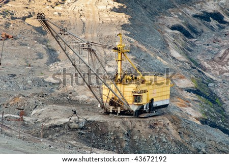 Heavy equipment digs ore inside an enormous open pit mine of Kursk Magnetic Anomaly - stock photo