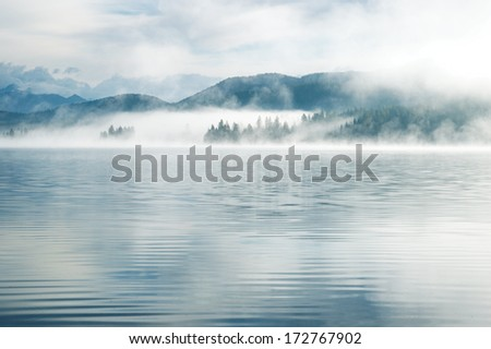 Heavy fog in the early morning on a mountain lake Early morning on Yazevoe lake in Altai mountains, Kazakhstan  - stock photo